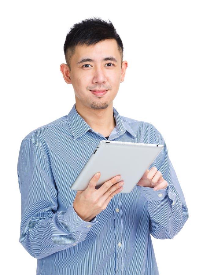 Молодой человек касаясь на таблетке стоковое фото rf