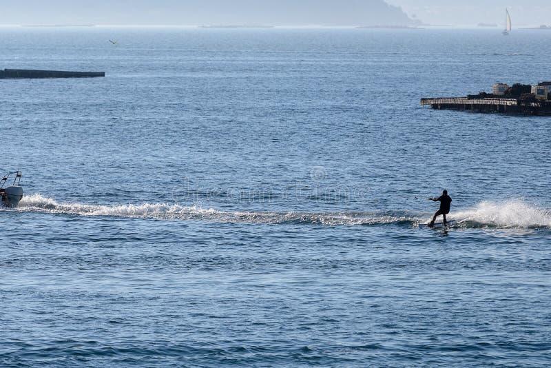 Молодой человек катается на лыжах в море стоковое изображение rf