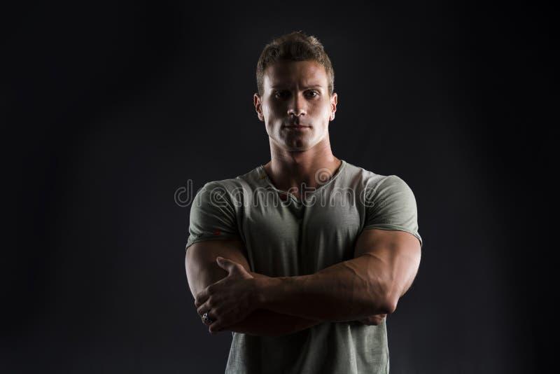 Молодой человек красивой мышечной пригонки на темной предпосылке с кормовым выражением стоковое фото rf