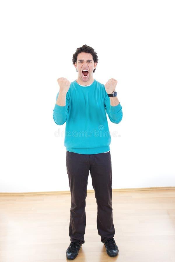 Молодой человек кричащий с сжатыми кулаками стоковое фото rf