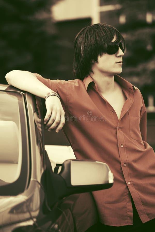 Молодой человек моды стоя около его обратимого автомобиля стоковое фото