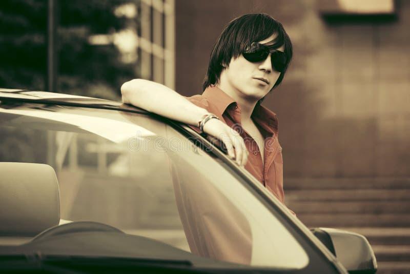 Молодой человек моды стоя около его обратимого автомобиля стоковые изображения rf