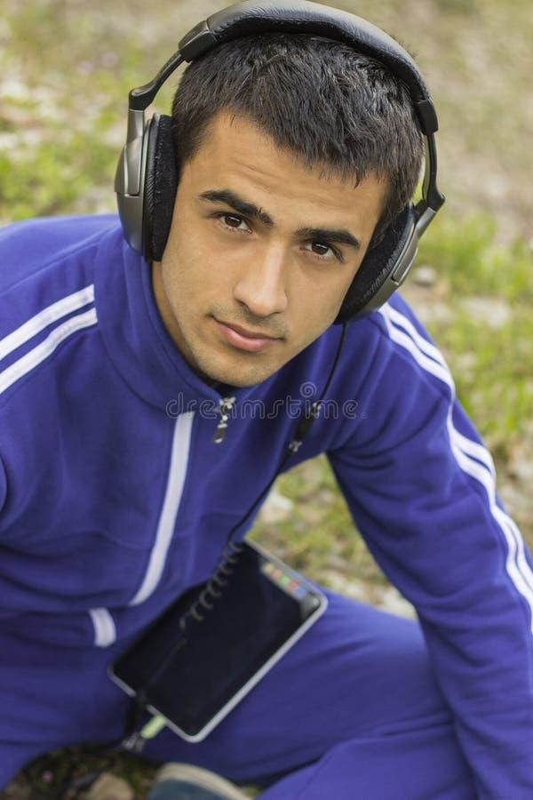 Молодой человек наслаждаясь слушать к музыке на таблетке стоковое изображение