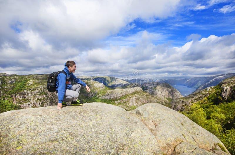 Молодой человек на горе восхищая взгляд над Lysefjord Норвегия стоковое изображение rf