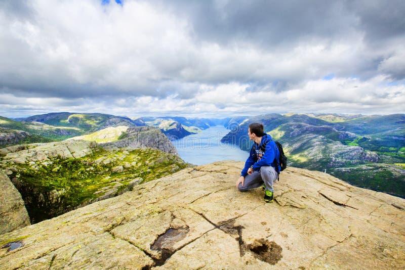 Молодой человек на горе восхищая взгляд над Lysefjord Норвегия стоковая фотография rf