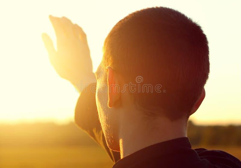 Молодой человек на заходе солнца стоковые фотографии rf