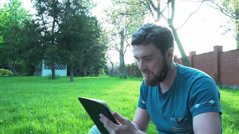 Молодой человек на зеленой лужайке с таблеткой Студент на лужайке отдыхая с таблеткой видеоматериал