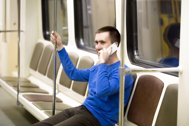 Молодой человек на мобильном телефоне в метро стоковое фото rf