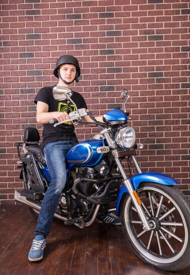 Молодой человек на мотоцикле перед кирпичной стеной стоковые изображения rf