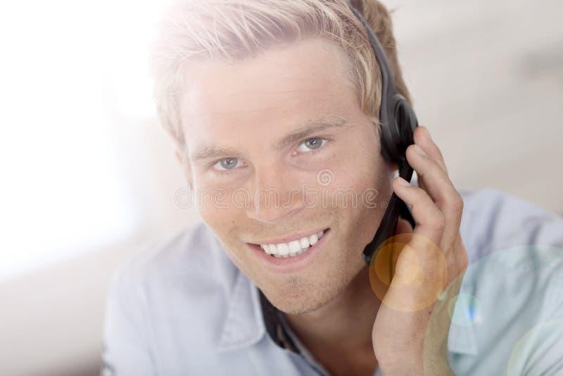 Молодой человек на попечении обслуживания клиента стоковое изображение rf