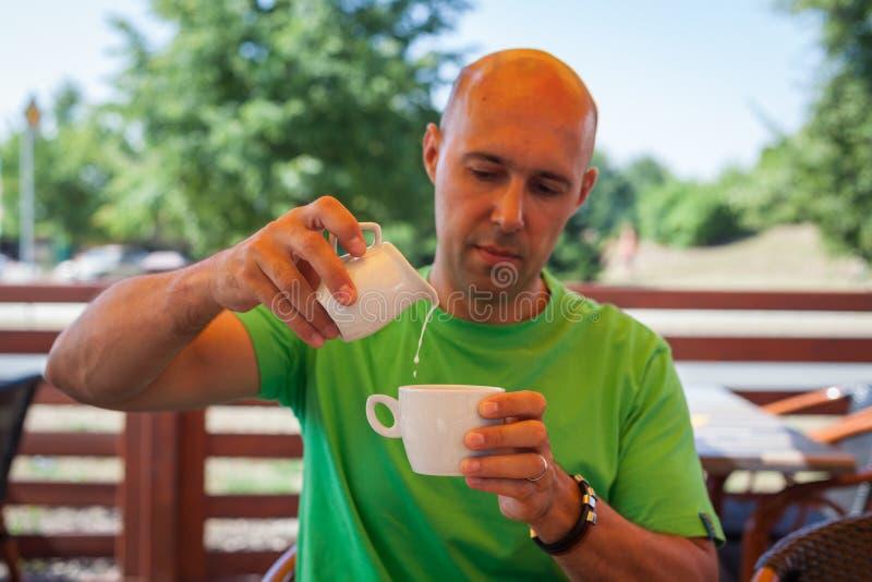 Молодой человек на террасе кафа в молоке лета лить в кофе стоковые изображения