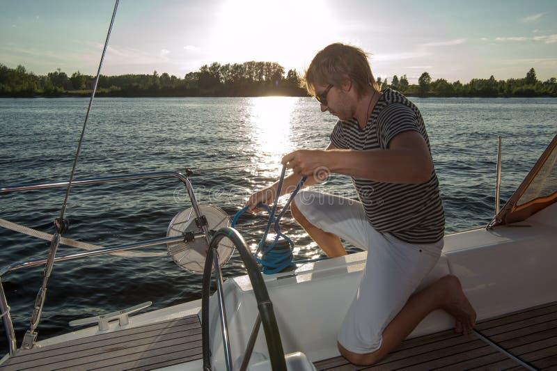 Молодой человек на яхте стоковые фото