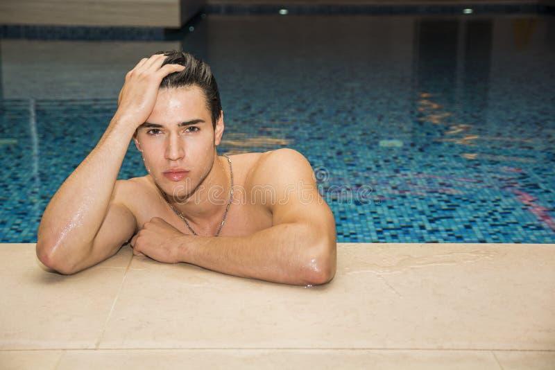 Молодой человек ослабляя в бассейне стоковая фотография rf