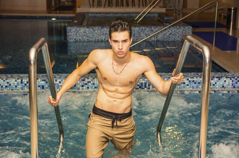 Молодой человек ослабляя в водовороте курорта стоковые фото
