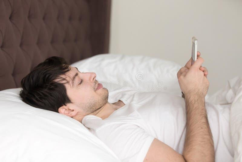 Молодой человек ослабляя в кровати дома используя передвижной smartphone стоковые фотографии rf