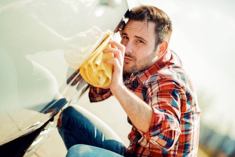 Молодой человек очищая его автомобиль стоковое изображение rf