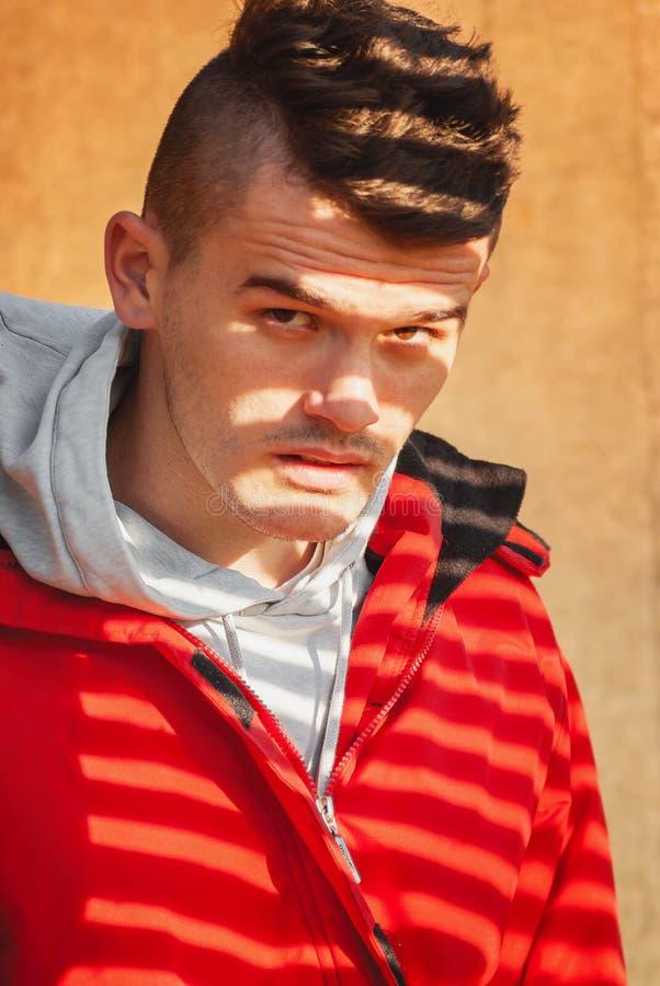 Молодой человек представляя в красной куртке покрытой с красивой тенью стоковые фотографии rf