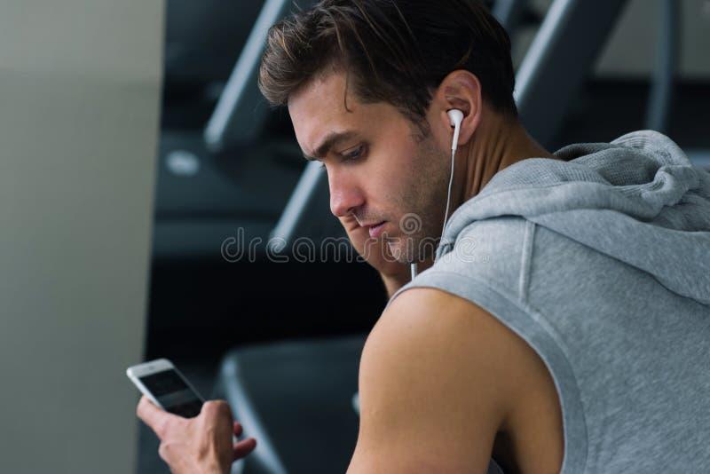Молодой человек принимая пролом после его разминки и слушая к музыке на его телефоне стоковая фотография rf