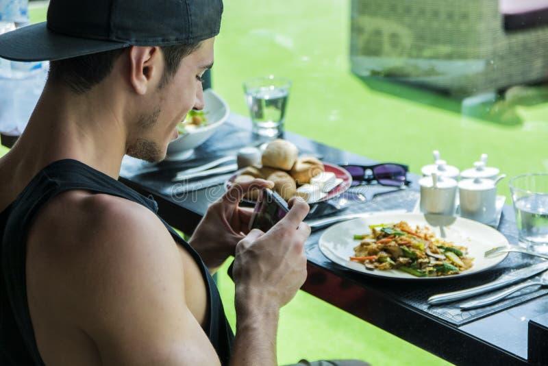 Молодой человек принимая фото еды на обедающий стоковое изображение