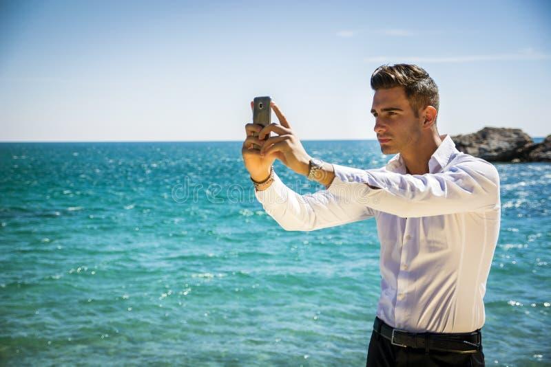 Молодой человек принимая фото Selfie на пляж стоковая фотография rf