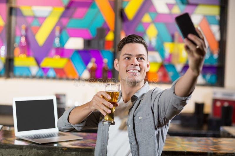 Молодой человек принимая selfie пока имеющ стекло пива стоковая фотография rf