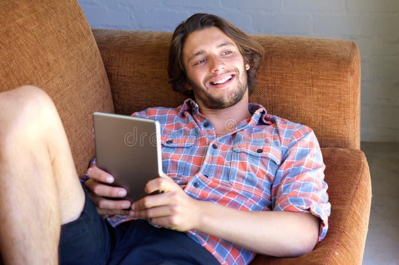 Молодой человек при борода лежа на софе с цифровой таблеткой стоковые фотографии rf