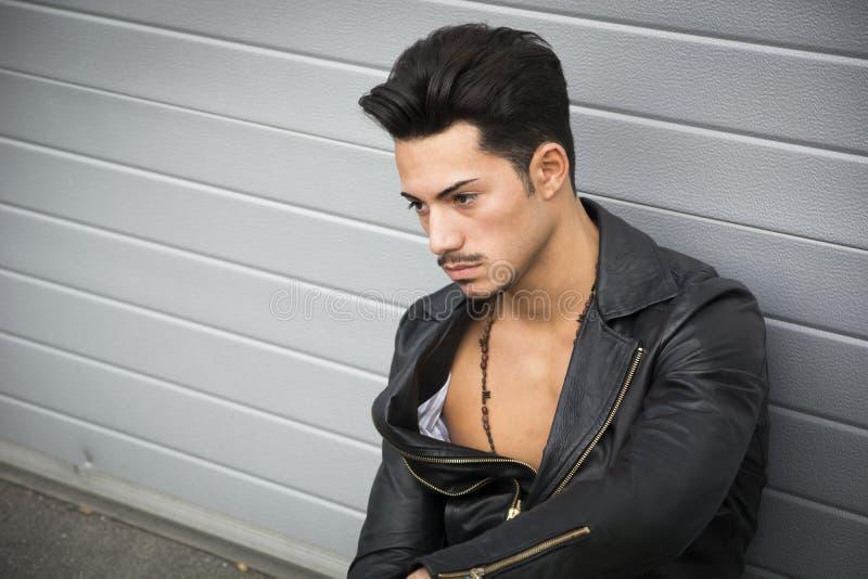 Молодой человек при кожаная куртка смотря прочь, сидящ на том основании стоковое изображение