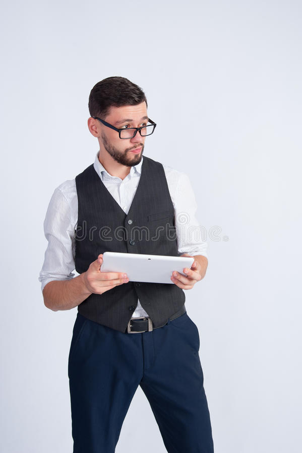 Молодой человек при стекла стоя с таблеткой стоковое изображение rf