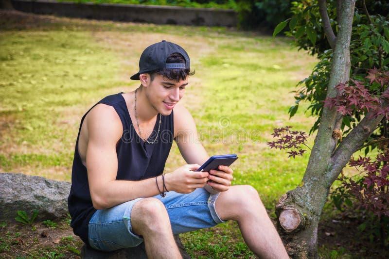 Молодой человек при таблетка или читатель Ebook ослабляя на стоковое изображение