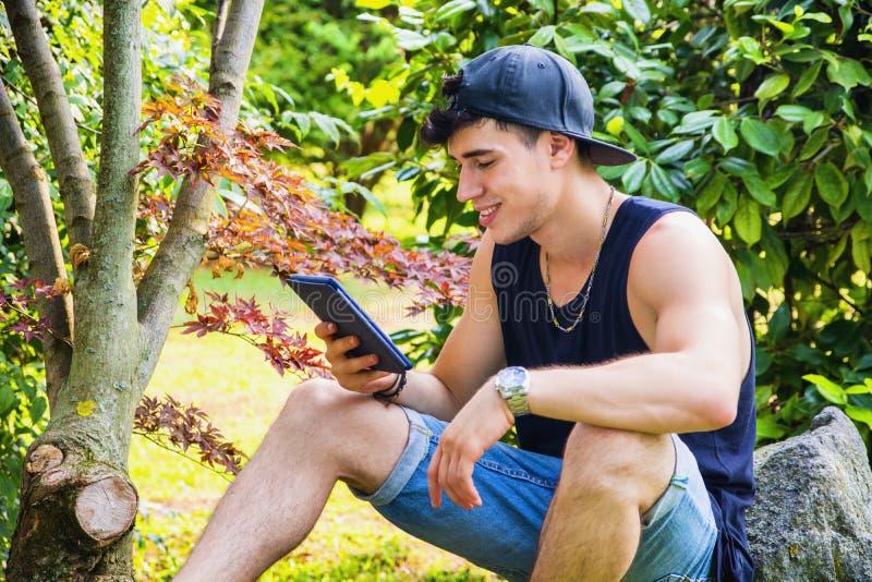 Молодой человек при таблетка или читатель Ebook ослабляя на стоковые фото