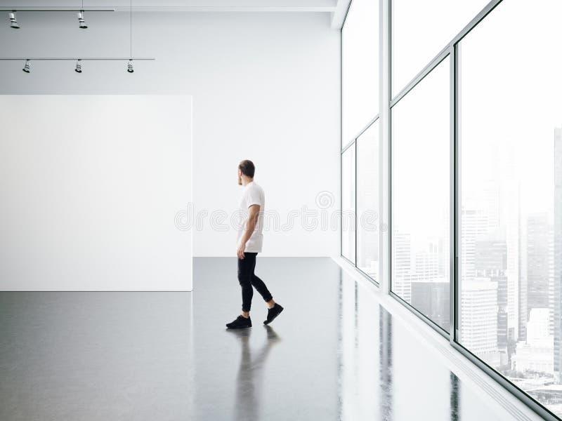 Молодой человек пустой галереи внутренний и идя стоковое изображение