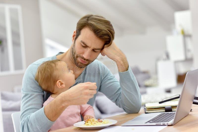Молодой человек работая на компьтер-книжке и подавая младенце стоковые фотографии rf