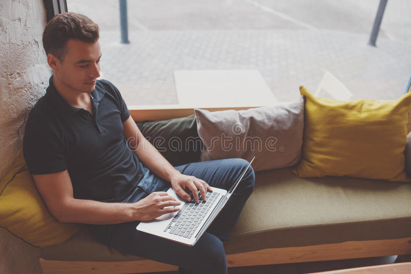 Молодой человек работая на компьтер-книжке пока сидящ в удобном кресле стоковая фотография