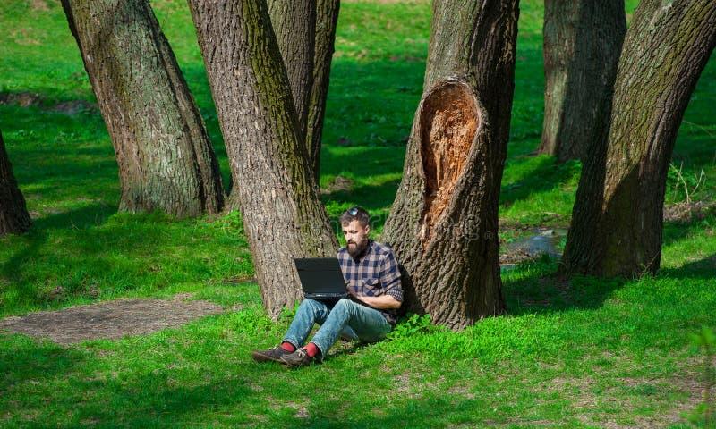 Молодой человек работая с компьтер-книжкой в весне park01 стоковое изображение rf