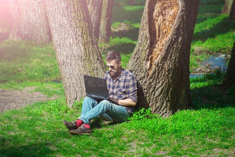 Молодой человек работая с компьтер-книжкой в весне park02 стоковое изображение rf
