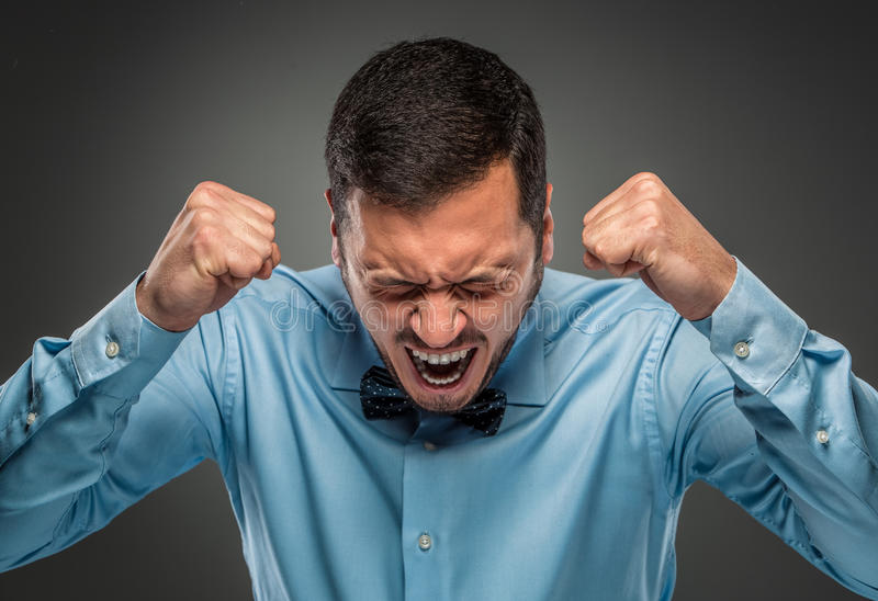 Молодой человек сердитой осадки портрета в голубой рубашке, связи бабочки стоковые фото