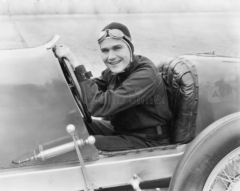 Молодой человек сидя в гоночной машине с большой улыбкой (все показанные люди более длинные живущие и никакое имущество не сущест стоковые изображения
