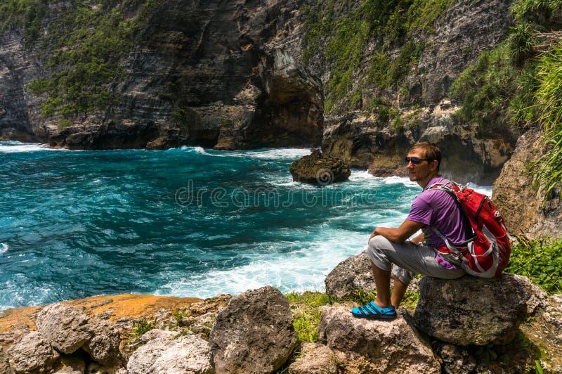 Молодой человек сидя в красивой бухте на утесе и наблюдая морем стоковая фотография