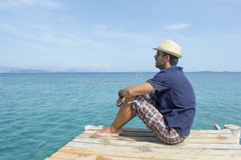 Молодой человек сидя на доке смотря голубое море стоковое фото rf