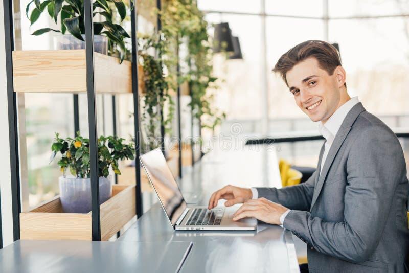 Молодой человек сидя на столе в офисе, работая на портативном компьютере стоковое изображение rf
