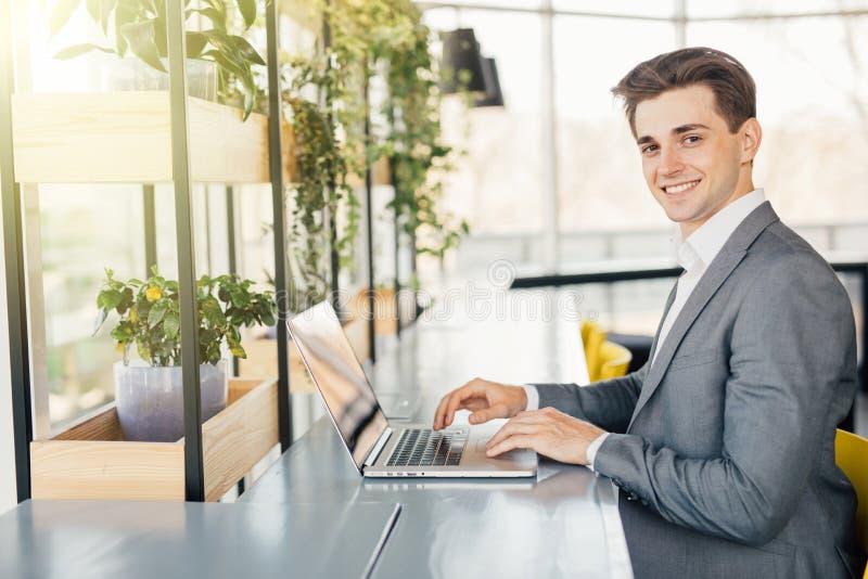 Молодой человек сидя на столе в офисе, работая на портативном компьютере стоковое фото