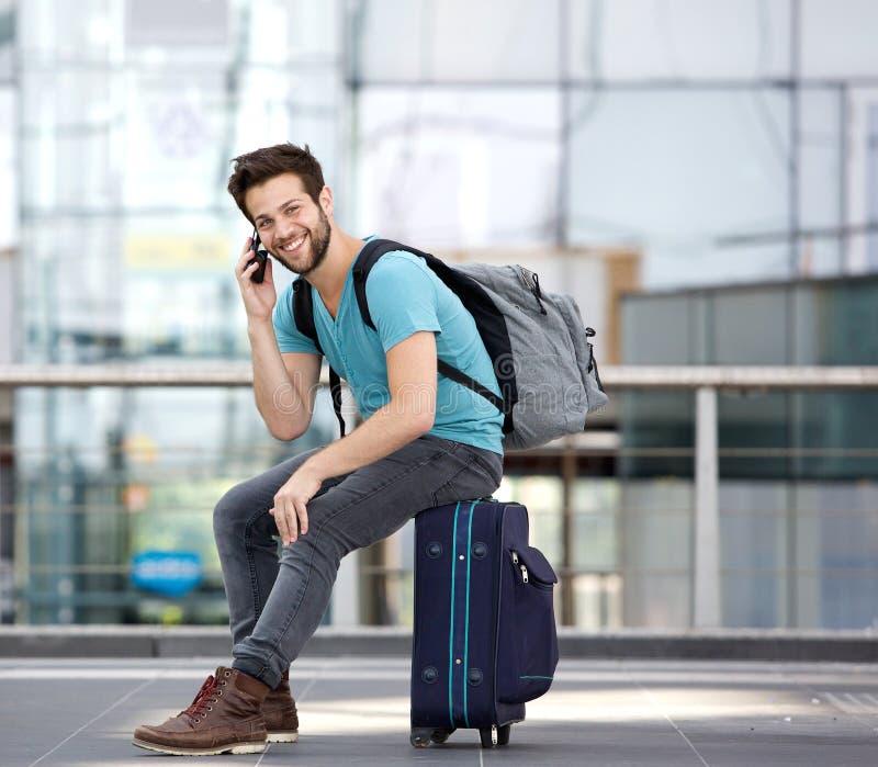Молодой человек сидя на чемодане и вызывая мобильным телефоном стоковые фото