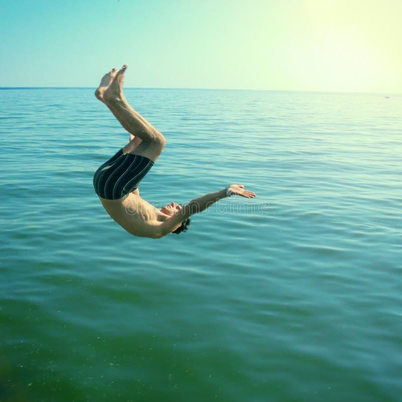 Молодой человек скача в море стоковая фотография