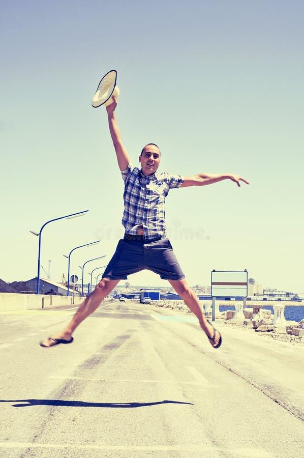 Молодой человек скача с соломенной шляпой в его руке стоковые фотографии rf