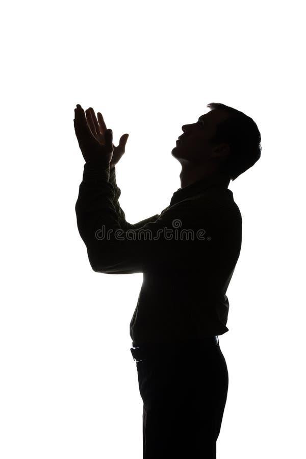 Молодой человек смотря вверх с надеждой и запросом - силуэтом стоковые фото