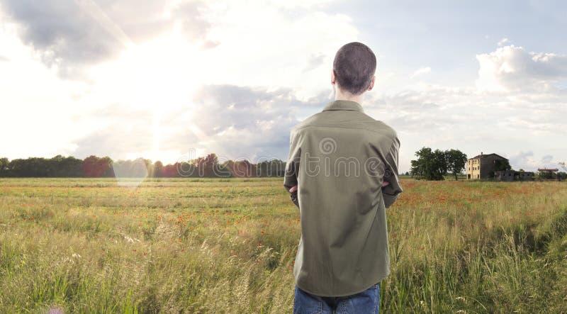 Молодой человек смотря заход солнца стоковая фотография