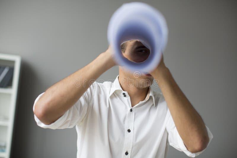 Молодой человек смотря через spyglass стоковые фото