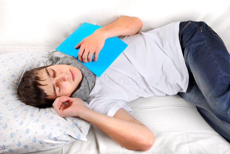 Молодой человек спит с книгой стоковая фотография