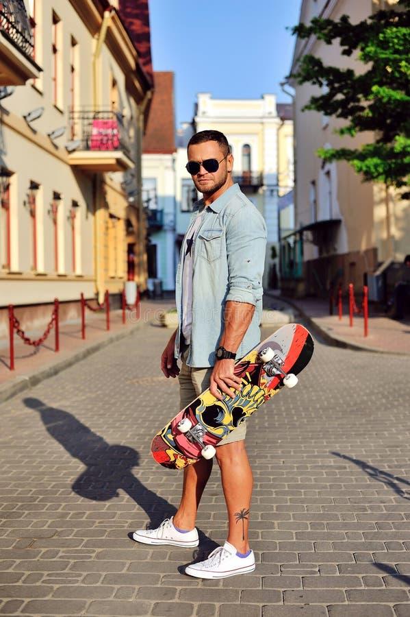 Молодой человек стиля битника с скейтбордом стоковая фотография rf