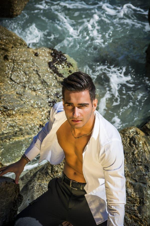Молодой человек стоя в воде морским путем или береге океана, стоковое изображение rf